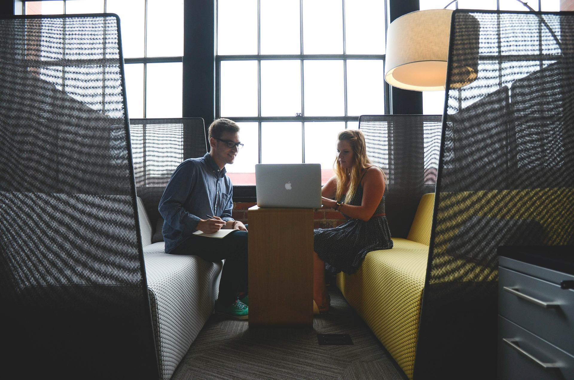 un homme et une femme face à face devant un ordinateur portable